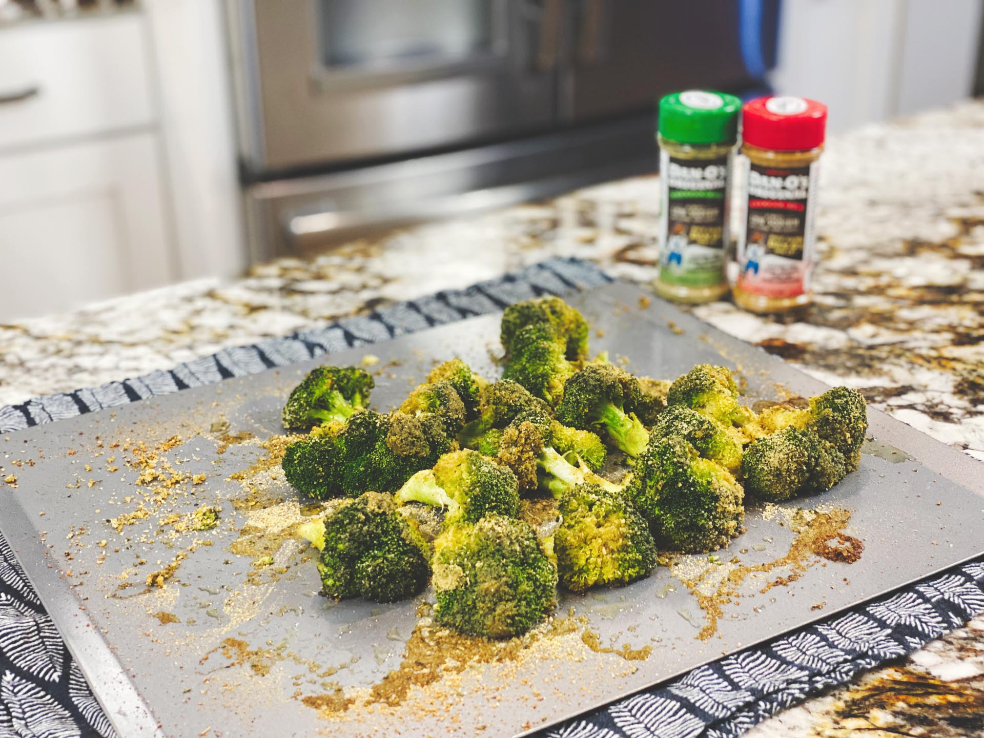 Image of baked broccoli with danos seasoning in the background