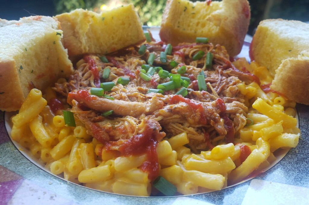 Image of honey sriracha chicken on mac N cheese with garlic bread