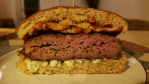 Image of cooked black N blue burger with bacon and fried onions