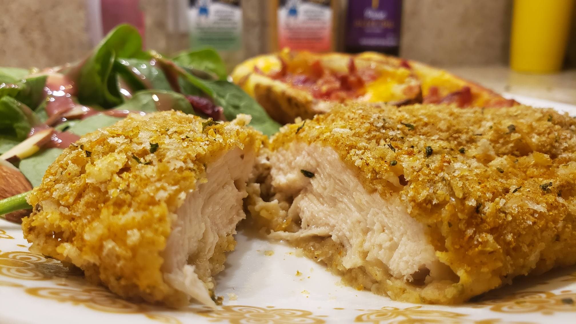Image of parmesan crusted chicken on a plate with sides