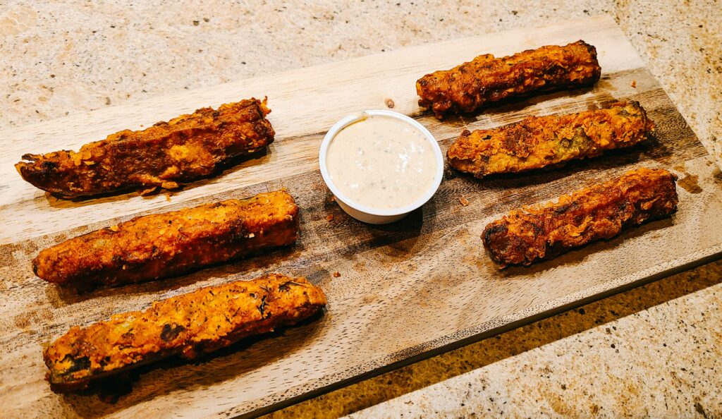 Fried pickle spears on a cutting board with ranch