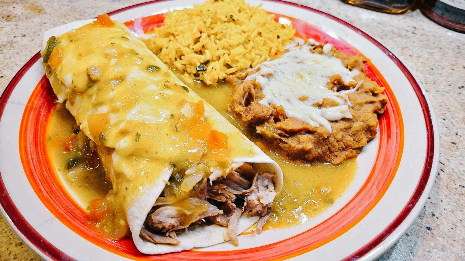 pork chili verde smothered burrito on a plate